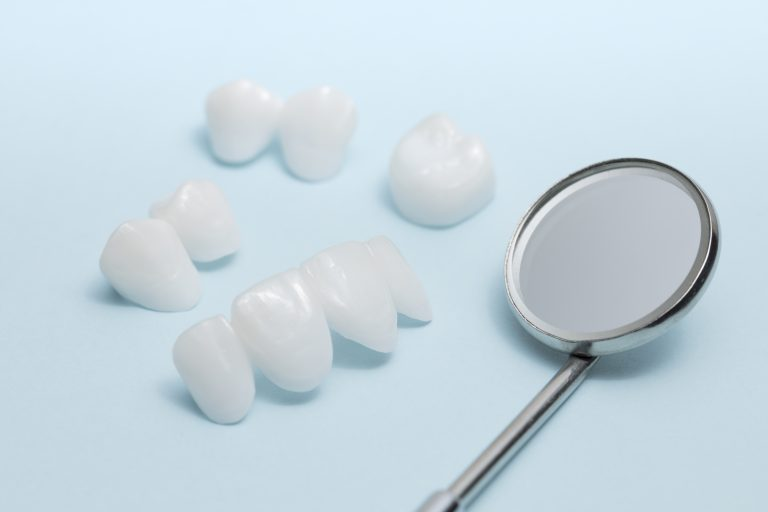 Dental Mirror And Dentures On A Light Blue Background