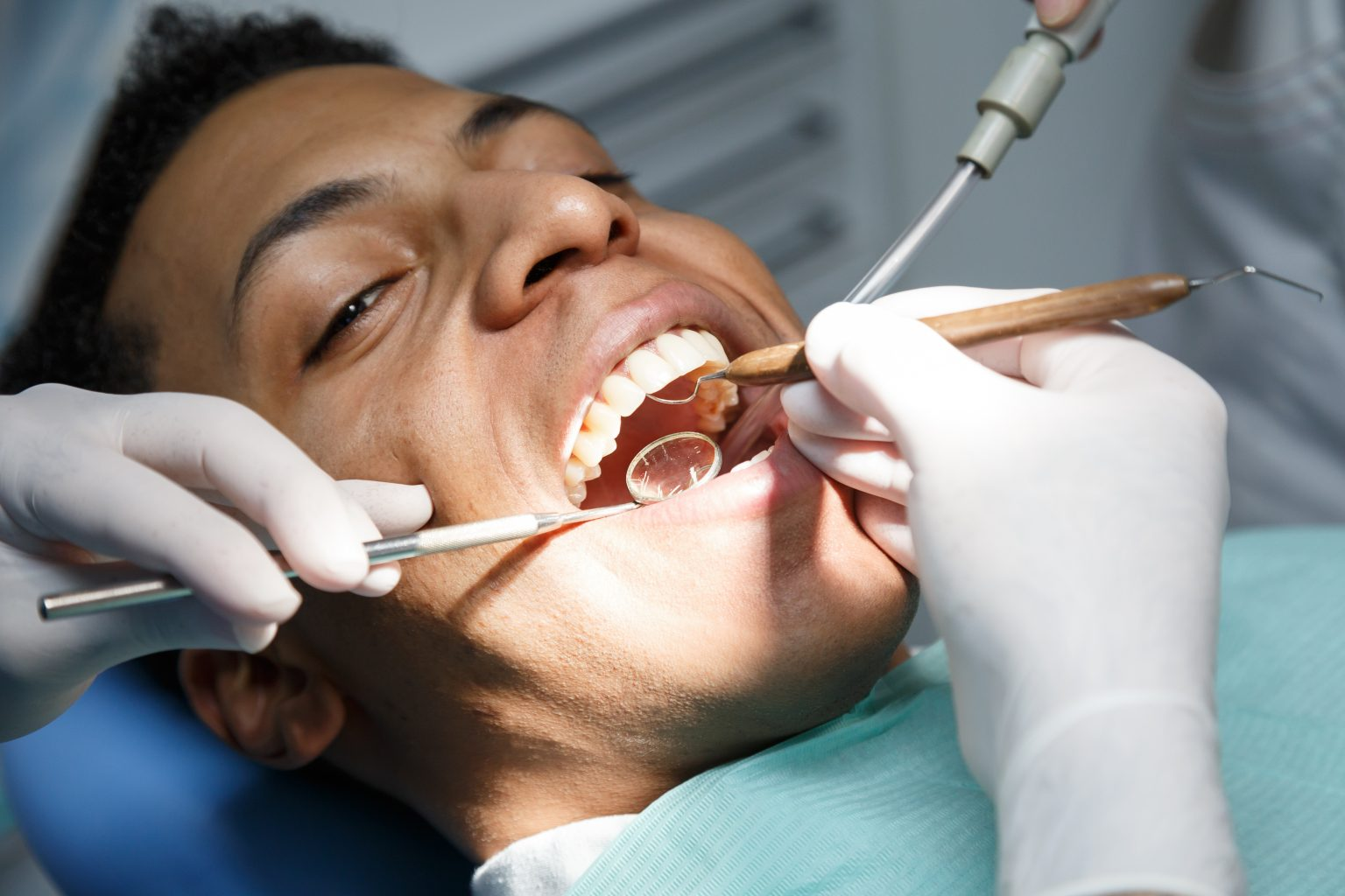 Dentist Examining Oral Cavity Of Young African American Man Working In In Dental Clinic With Assistant.
