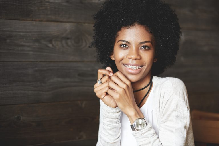 close up shot of attractive happy cheerful dark skinned young woman looking and smiling at the camera, showing white teeth with braces, holding hands at her face. human face expressions and emotions