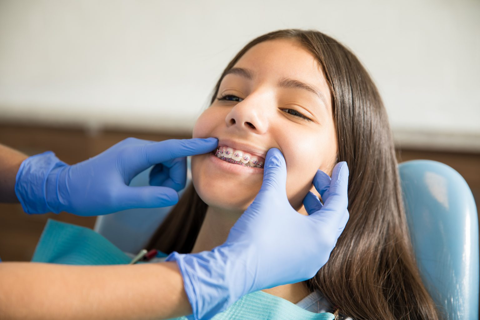 girl with braces being examined by dentist in clinic