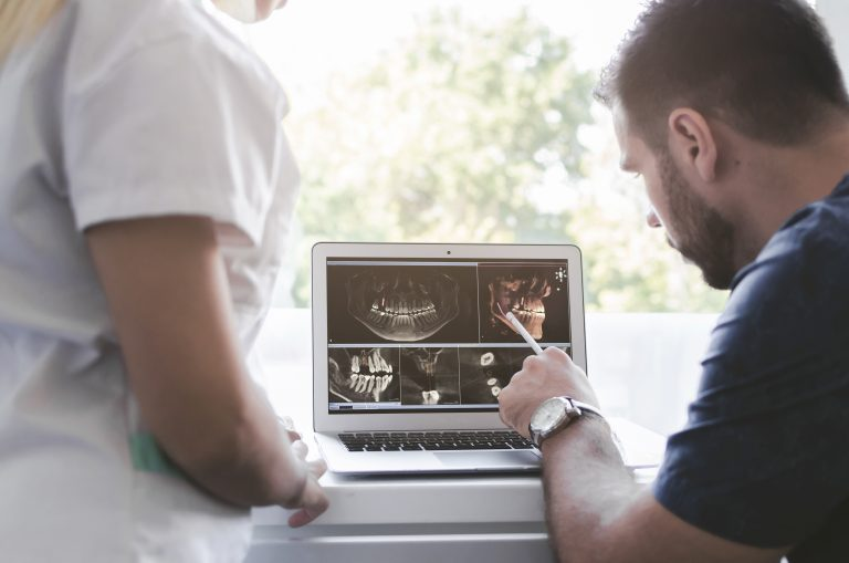 male and female dentist looking at xray